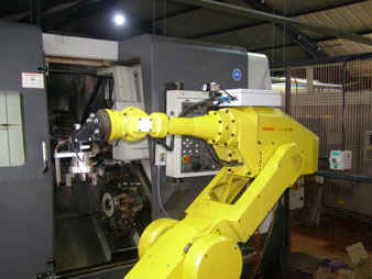Reconditioned Fanuc S700 robot tending an auto-lathe